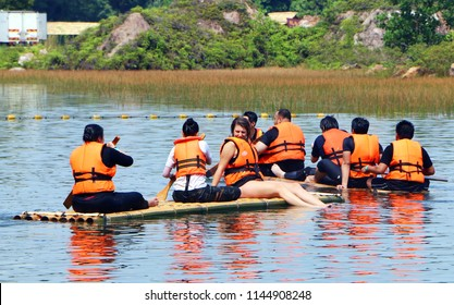 Banting, Selangor, Malaysia - July 28, 2018 : Tourist rowing and sitting on the bamboo raft floating at a lake at Tadom Resort Hill in Banting, Selangor.