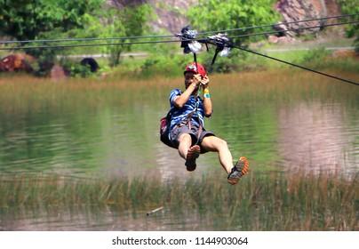 Banting, Selangor, Malaysia - JULY,28, 2018 : Men enjoying zip-line flying over the forest at Tadom Hill Resort in Banting, Selangor.