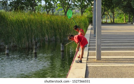 Banyoles, Catalonia/Spain; Agost 19 2019: Chinese little boys playing fishing near a pond on a summer day; using a fishing net ant a stick like fishing rod.