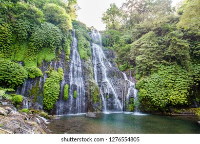 Banyumala twin waterfalls with cascades among green tropical trees and plants on the north of Bali island, Indonesia