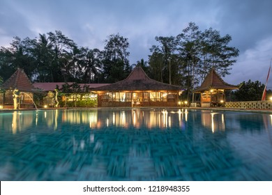 Banyuwangi, Indonesia - Architecture wooden resort bali style with swimming pool and illumination in dusk at Ijen island