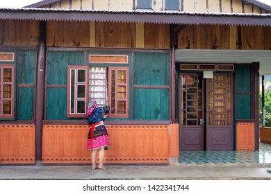 Bao Loc, Lam Dong province, Vietnam - Jun 2, 2019: image of H'Mong ethnic woman next to their newly built house in Bao Loc, Lam Dong province, Vietnam