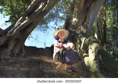 Bao Loc town, Lam Dong Province, Vietnam - February 28, 2017: beautiful woman  sitting for relaxing under the old tree in the forest of the national park in Bao Loc town, Lam Dong province, Vietnam.