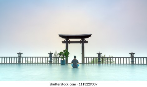Bao Loc, Vietnam - May 15th, 2018: The man meditating in front temple as a way to relax soul into realm of spiritual deposition peace where Buddha door in morning in Bao Loc, Vietnam