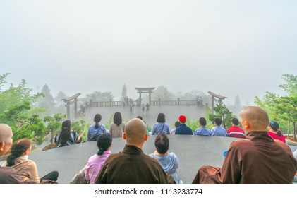 Bao Loc, Vietnam - May 15th, 2018: Tourists meditating in front temple as a way to relax soul into realm of spiritual deposition peace where Buddha door in morning in Bao Loc, Vietnam