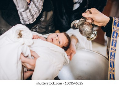 Baptism baby. Cute little head of a girl under holy water at christening ceremony with priest in church and bible