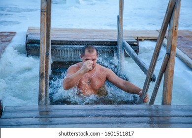 Baptism, bathing in the winter ice hole, beautiful winter landscape with an ice cross on a frozen river