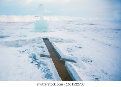Baptism, bathing in the winter ice hole, beautiful winter landscape with an ice cross on a frozen river, Traditional ice swimming in Orthodox church Holy Epiphany day.