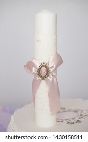 Baptismal delicate white candle wrapped with a pink ribbon cameo, in preparation for the baptism, first of seven Sacraments in the Orthodox Christian Church, symbolic element for this religious rite