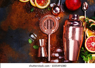 Bar accessories, drink tools and cocktail ingredients - red oranges, lime, minta and ice cubes on rusty stone table. Flat lay style