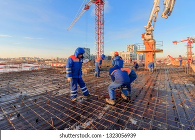 Bar bender fixing steel reinforcement for house concrete floor slab. construction worker Concrete pouring during commercial concreting floors of building in site and Civil Engineer. Moscow 02/2019.