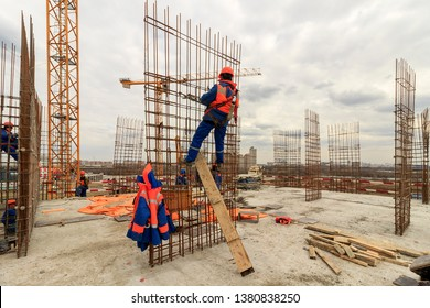 Bar bender fixing steel reinforcement for house concrete floor slab. construction worker Concrete pouring during commercial concreting floors of building in site and Civil Engineer. Moscow 04/2019.