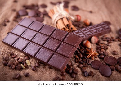 bar of chocolate with cinnamon and coffee beans on a burlap background
