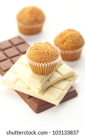 bar of chocolate and muffin isolated on white