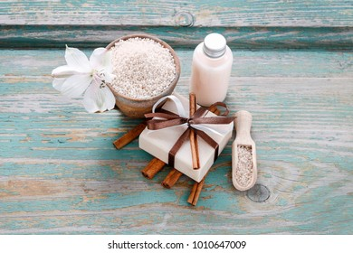 Bar of cinnamon handmade soap and cup of sea salt. Bottle with liquid soap in the background.