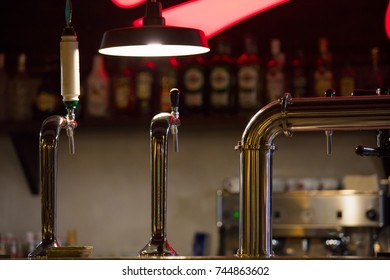 bar counter with beer taps and lamp on wall background with bottles