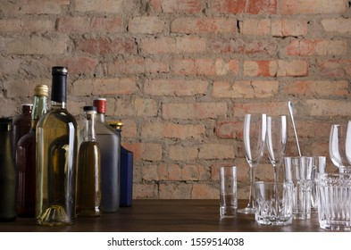 Bar counter and bottle of drinks, glassware on it, vintage red brick wall.Empty space for text
