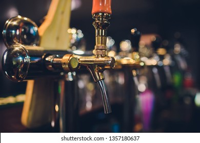 The bar counter with bottles and apparatus for dispensing beer. Apparatus for dispensing beer at the bar. Pub. The bar in the restaurant. Apparatus for dispensing beer in a restaurant.