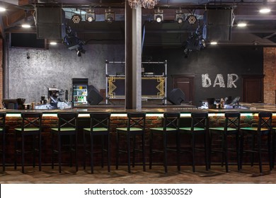 bar counter with bar chairs in loft style design, strobe light on dark ceiling