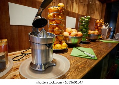 Bar counter with electrical juicer, spiral holders and bowls with oranges and apples.