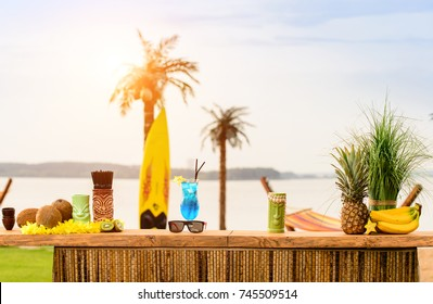 Bar counter on the beach at Hawaii. Glasses with cocktails, coconut, sun glasses lie on the table. Concept of relaxing, preparation and summer