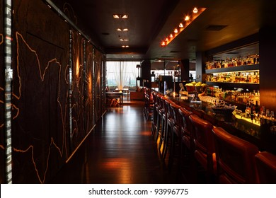 bar counter with red tall chairs in empty comfortable restaurant; lot of drinks on shelves