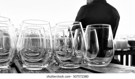 Bar drink glasses lined up in rows. Close up. Bartender seen from the back. Black and white image