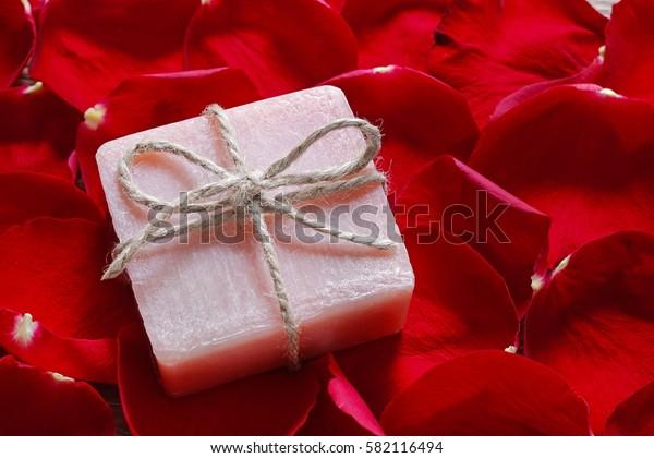 Bar of handmade soap lying on rose petals.