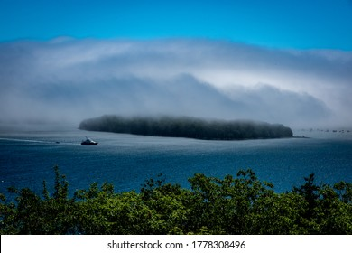 Bar Harbor, Maine, USA, Acadia National Park, July 4, 2020. A large fog bank like a giant tsunami covers much of an island in the Atlantic Ocean