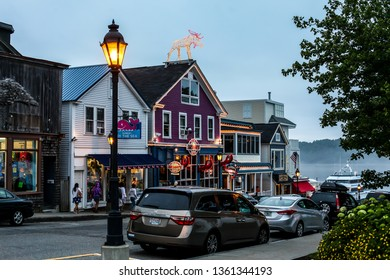 BAR HARBOR, MAINE, USA - JULY 9, 2013: Evening lights and street with cars and tourist in BAr Harbor downtown  near Frenchmans Bay.
