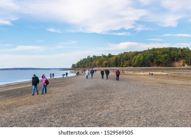 Bar Harbor, Maine / USA - October 9 2019: People walking across the sand bar that connects Bar Harbor to Bar Island, part of Acadia National Park.  The island is only accessible on foot at low tide.
