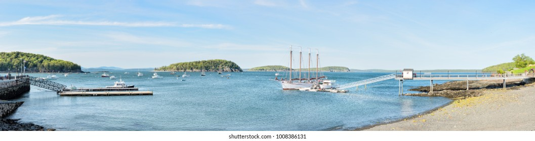 Bar Harbor, USA - June 8, 2017: Panorama panoramic view of tour ship sail boat, pier, shore, rocky beach, people in tourist village in summer