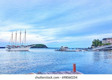 Bar Harbor, USA - June 8, 2017: Sunset in Bar Harbor, Maine village with Margaret Todd windjammer large sailboat approaching dock