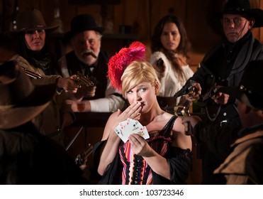 Bar maid with cards and people with guns aimed at her
