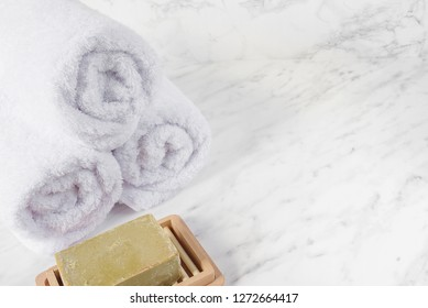 Bar of natural handmade organic soap and white terry towels on a marble background, with space for text