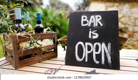 """Bar is open"" sign and vintage wooden crate full of wine bottles decorated with olive branches on a table. Festive party, wedding or other event."