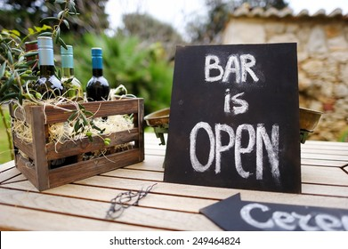 Bar is open sign and vintage wooden crate full of wine bottles decorated with olive branches on a table
