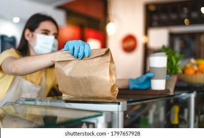 Propriétaire de bar travaillant uniquement avec les commandes à emporter lors de l'épidémie de virus de la couronne - Jeune travailleuse portant un masque chirurgical donnant un repas à emporter à ses clients - Concept de soins de santé et de boisson alimentaire