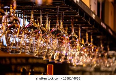 A bar rack hanging empty wineglasses.