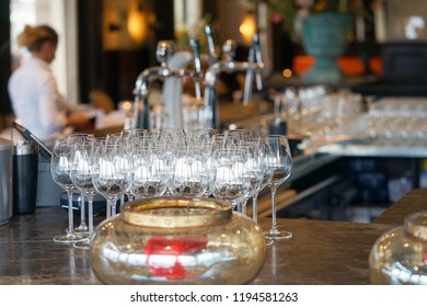 Bar rack with wine glasses. The barmaid serves wine glasses for a party in a bar, a hotel restaurant. The concept of service.