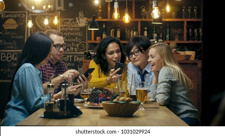 In the Bar/ Restaurant Birthday Party Celebration in Progress Beautiful Young People Show Their Mobile Phone Screens and Have Great Fun.