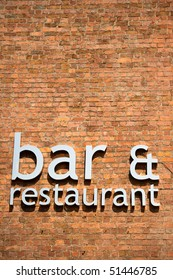 Bar and restaurant sign on brick wall with copy space.