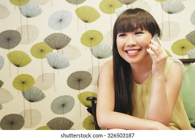 Bar smart casual young asian woman talking on smartphone. Happy female adult speaking on mobile phone.
