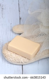 Bar soap and body scrub wisp on wooden back ground