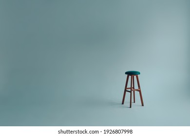 Bar stool with upholstered backless seat in an empty white room on a gray background.