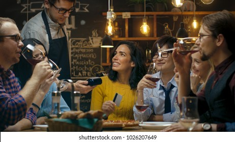 In the Bar Waiter Holds Card Machine and Beautiful Woman Pays for Her Order with Contactless Credit Card. She's Surrounded by Friends They all Have Great Time.