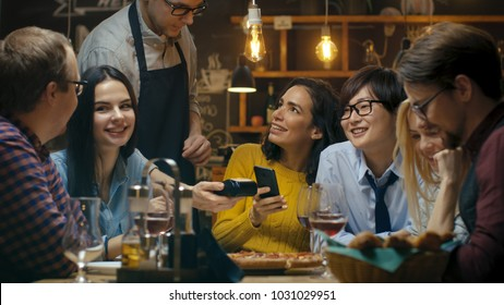 In the Bar Waiter Holds Credit Card Payment Machine and Beautiful Woman Pays for Her Order with Contactless Mobile Phone Payments System. She's Surrounded by Dear Friends and Has Time of Her Life.