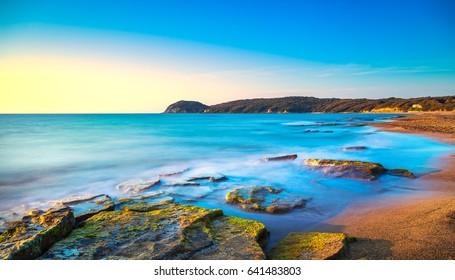 Baratti beach bay, travel destination, headland hill, rocks and sea on sunset. Maremma Tuscany, Italy, Europe. Long Exposure