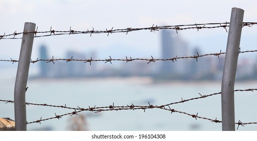 Barb wire fence with blue sky and city background