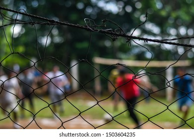 barb wire fence with latin men playing soccer/football out of focus in Guatemala
